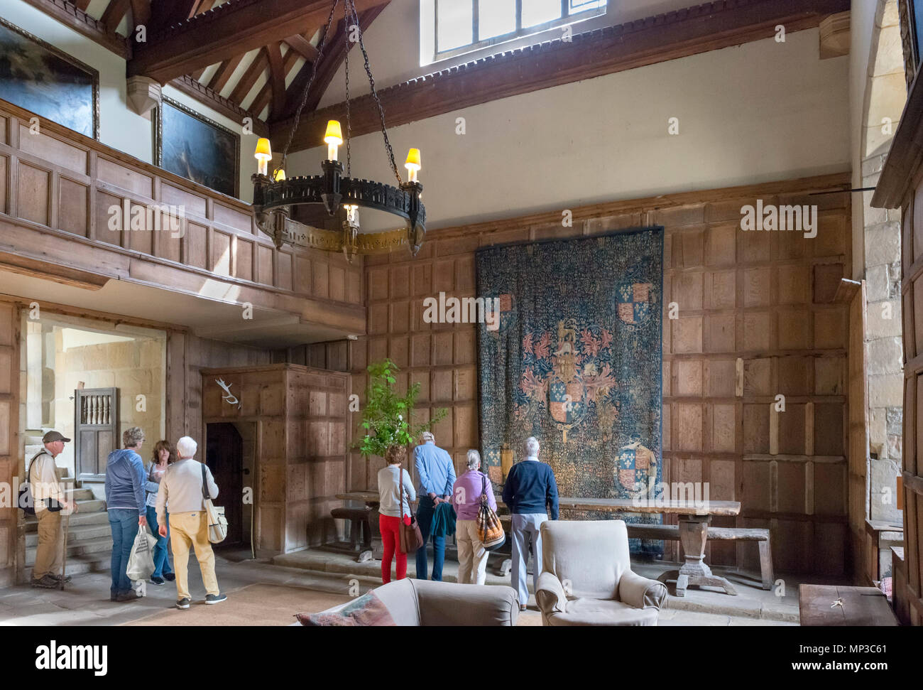 Visitors in the Hall at Haddon Hall, near Bakewell, Derbyshire, England, UK - Stock Image