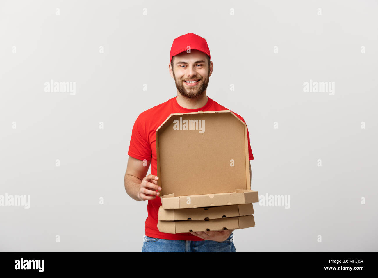 Pizza delivery concept. Young boy is delivering and showing pizza boxs in boxes. Isolated on white background - Stock Image