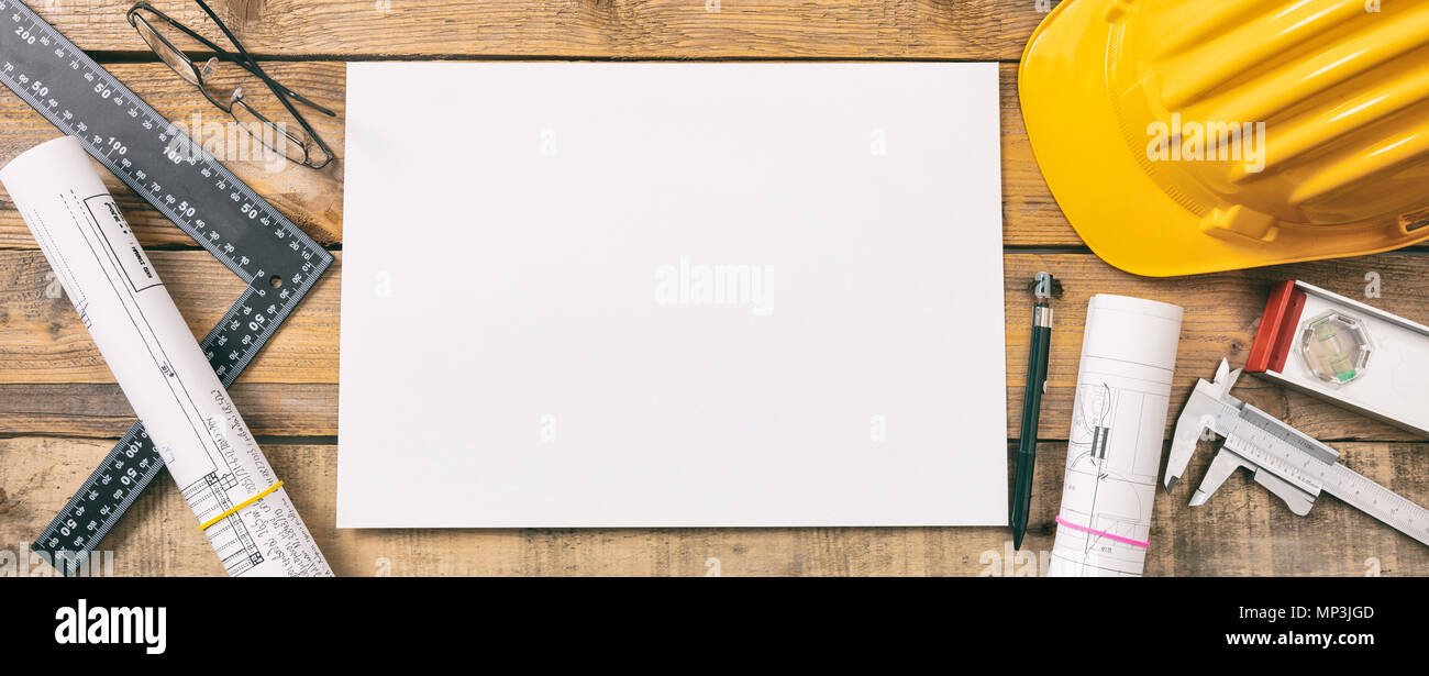 Architect workplace top view. White blank paper, project construction blueprints and engineering tools on wooden desk, copy space - Stock Image