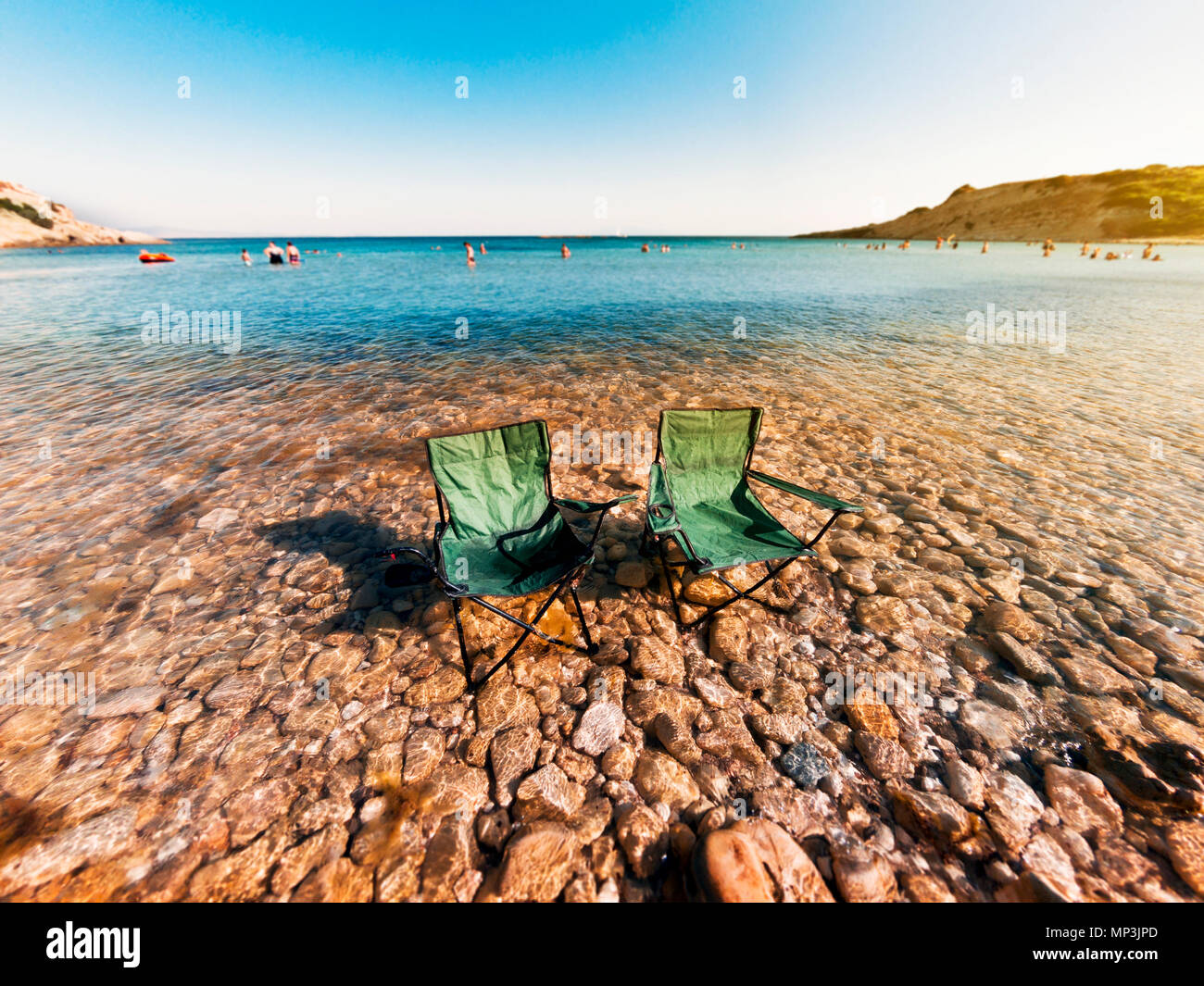 Two foldable chairs in the rocky water with a wide angle and a artificial shalow dof in Demircili bay Urla Izmir. - Stock Image