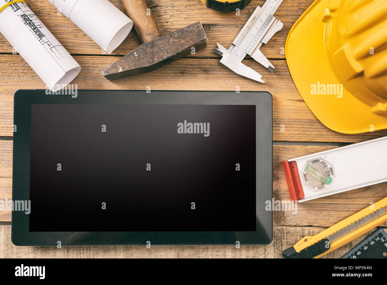 Architect workplace and technology. Tablet with black blank screen, project construction blueprints and engineering tools on wooden desk, copy space,  - Stock Image