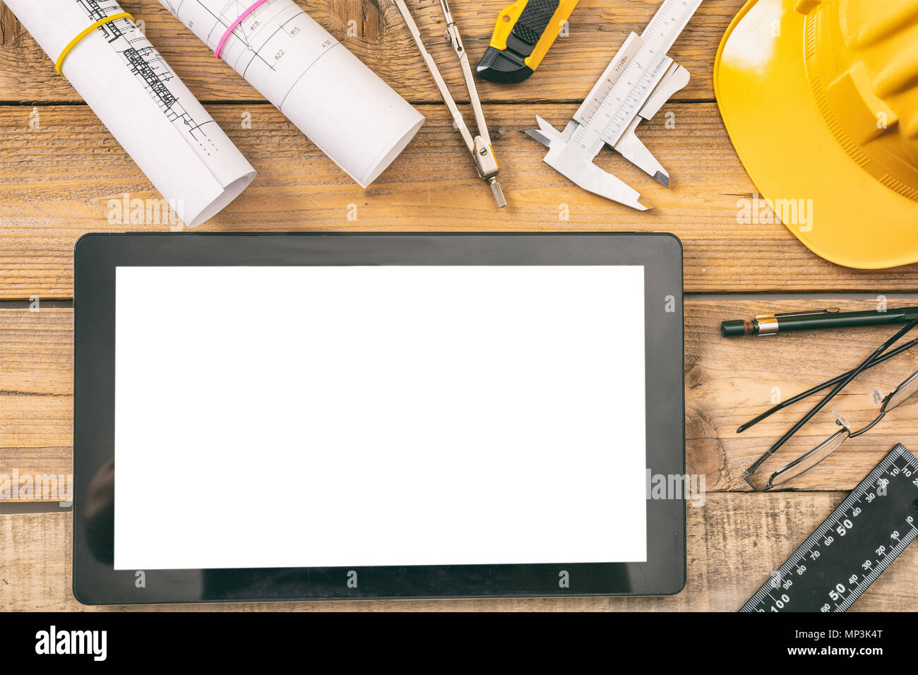 Architect workplace and technology. Tablet with white blank screen, project construction blueprints and engineering tools on wooden desk, copy space,  - Stock Image