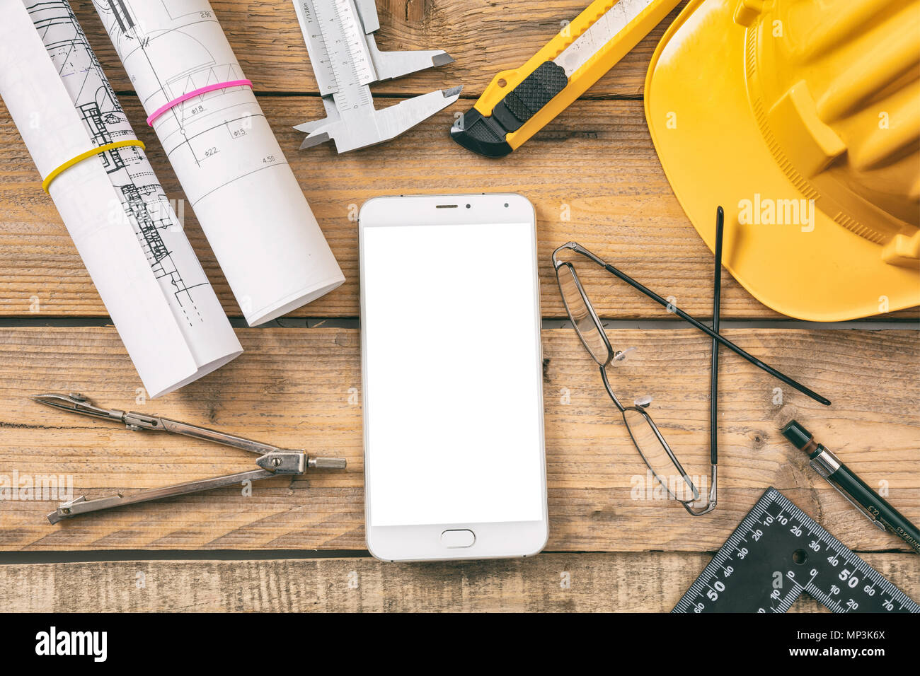 Architect workplace. Smart phone with white blank screen, project construction blueprints and engineering tools on wooden desk, top view, space for te - Stock Image