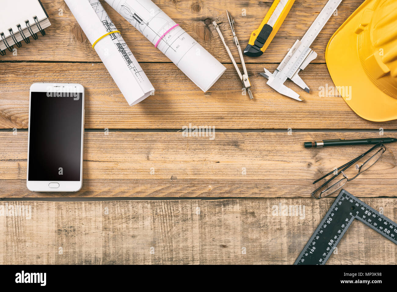 Architect workplace. Smart phone with black blank screen, project construction blueprints and engineering tools on wooden desk, copy space, top view - Stock Image