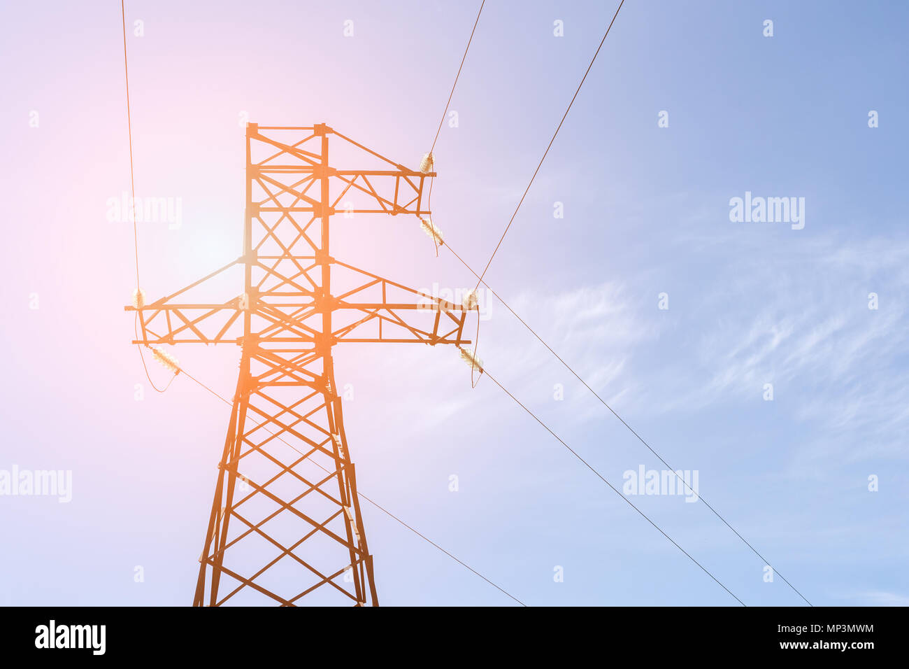 High-voltage electricity pylon with blue clear sky on background. Energy transmission - Stock Image