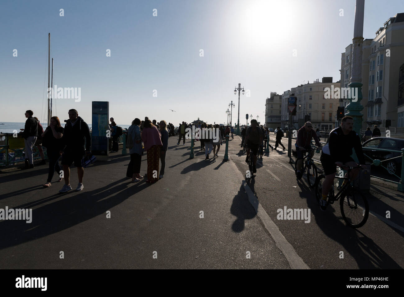 Shadowy pedestrians and cyclists on a busy path on Brighton seafront. Brighton, East Sussex, UK. - Stock Image
