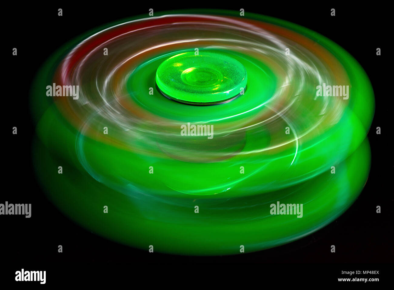Spinning Green and Red Fidget Spinner Toy. - Stock Image