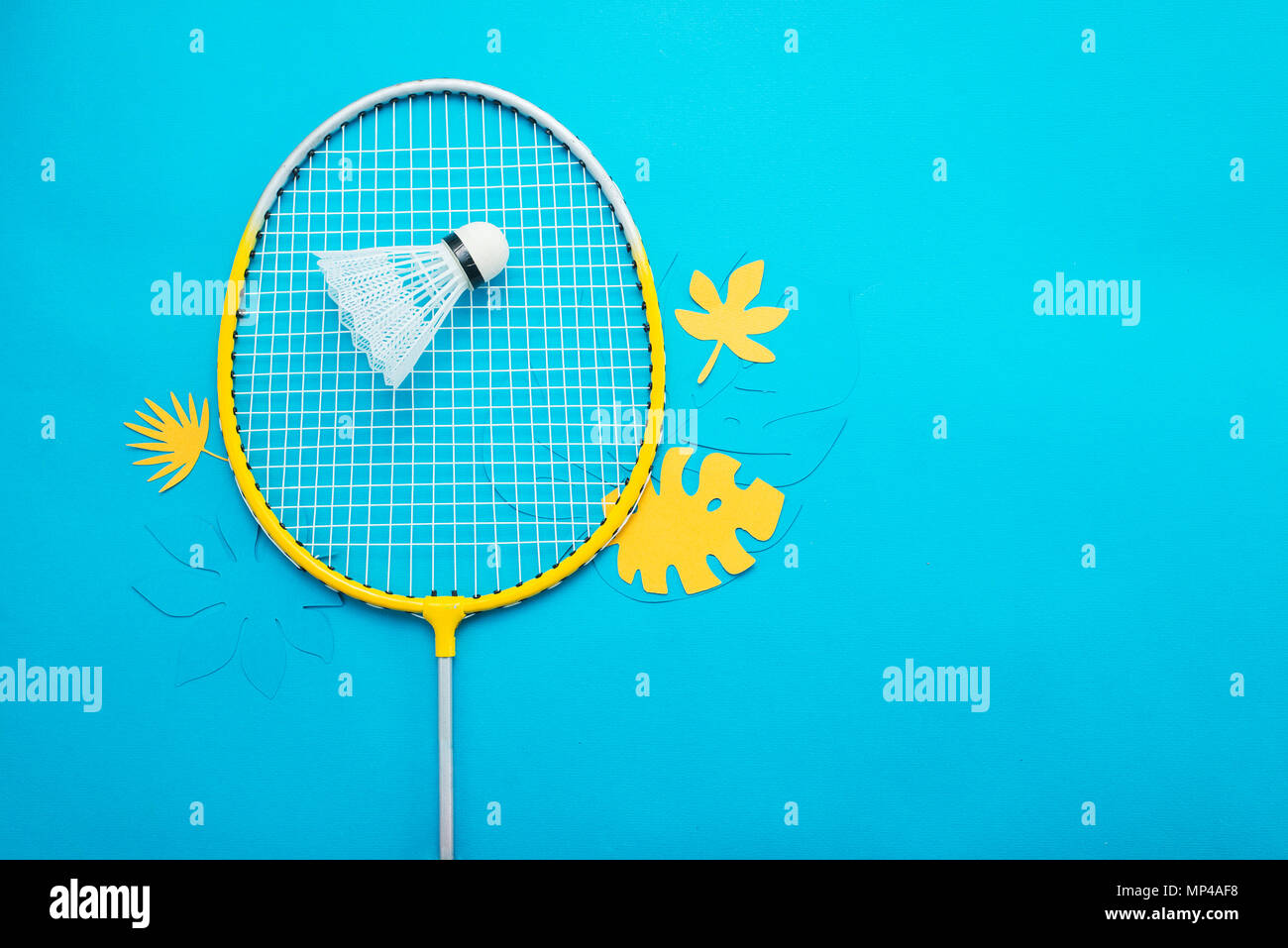 Badminton beach set and tropical leaves. Sports header on a bright blue background with copy space. Summer vacation flat lay - Stock Image