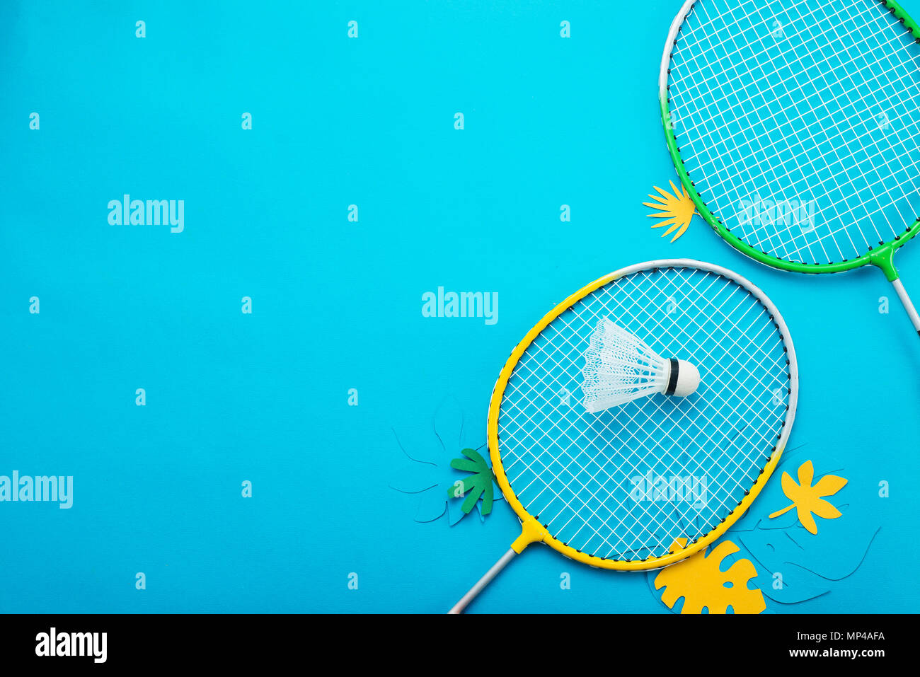 Badminton beach set and tropical leaves. Sports header on a bright blue background with copy space. Summer vacation flat lay Stock Photo