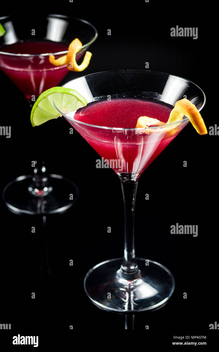 Alcohol drink cocktail Cosmopolitan with lime on black background - Stock Image