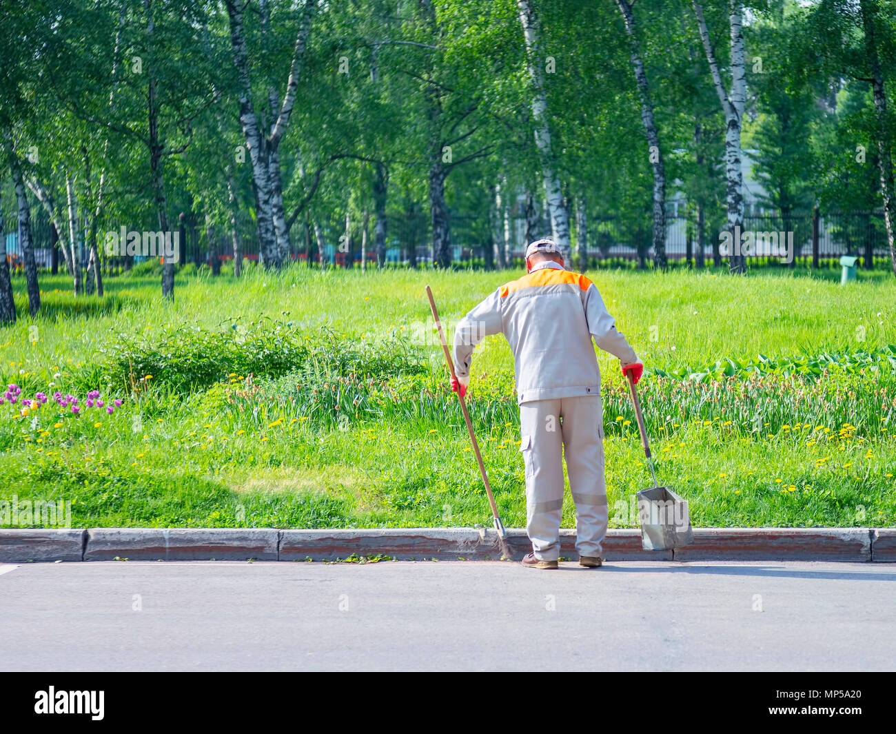 Selective focus road Sweeper cleaning walkway in the public park,copy space.l - Stock Image