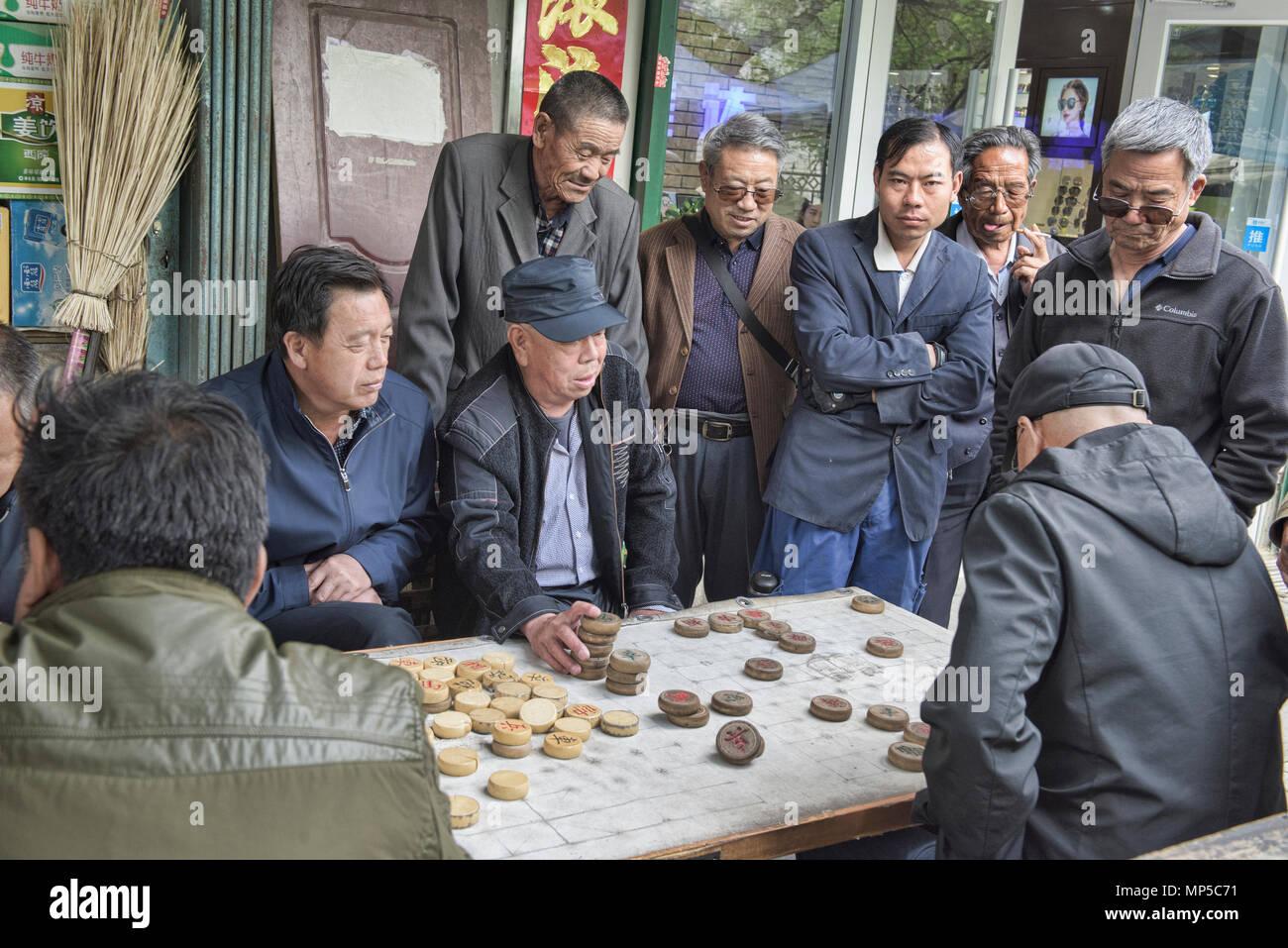 Old men playing Xiangqi, Chinese chess, Jiayuguan, Gansu, China - Stock Image