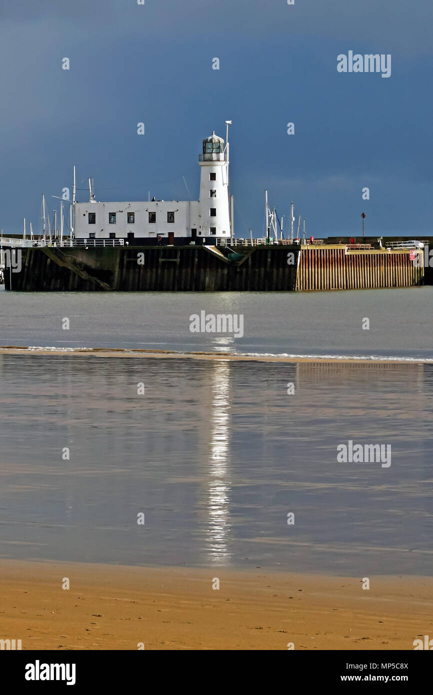 Scarborough's lighthouse mirrored in the wet sands of South Bay beach. - Stock Image