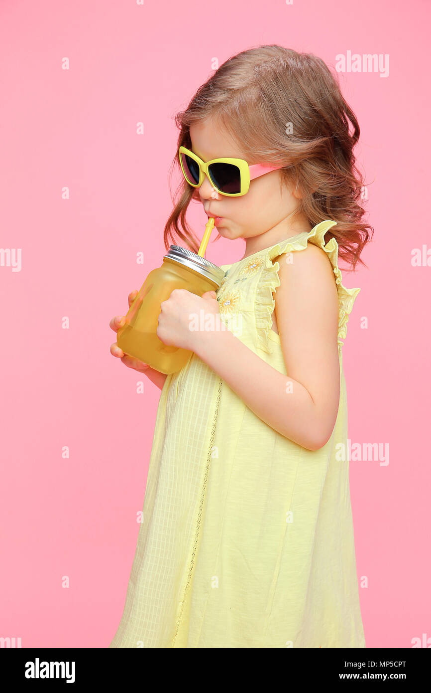 fa07751f4 Lovely little girl in summer outfit with drink Stock Photo ...