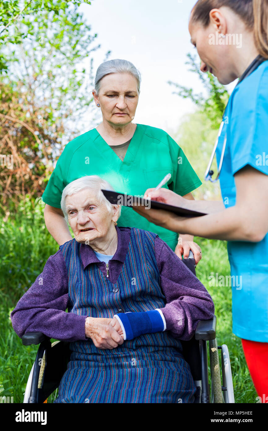 Elderly sick woman in wheelchair, medical nurses discussing treatment outdoor - Stock Image