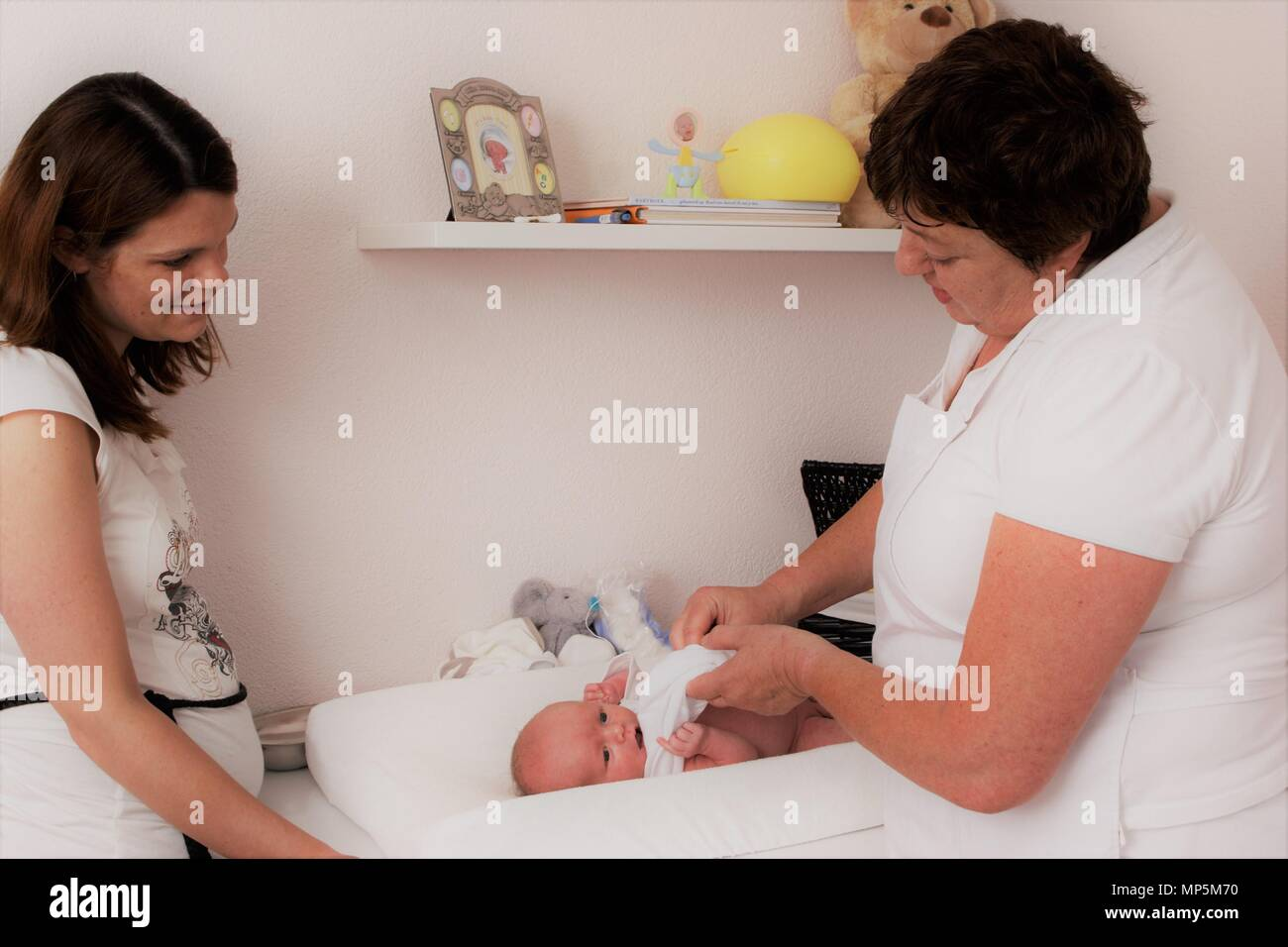 67a0f5f7578db Dutch maternity nurse dressing up newborn baby, assisting the new mother as  part of Dutch Kraamzorg.