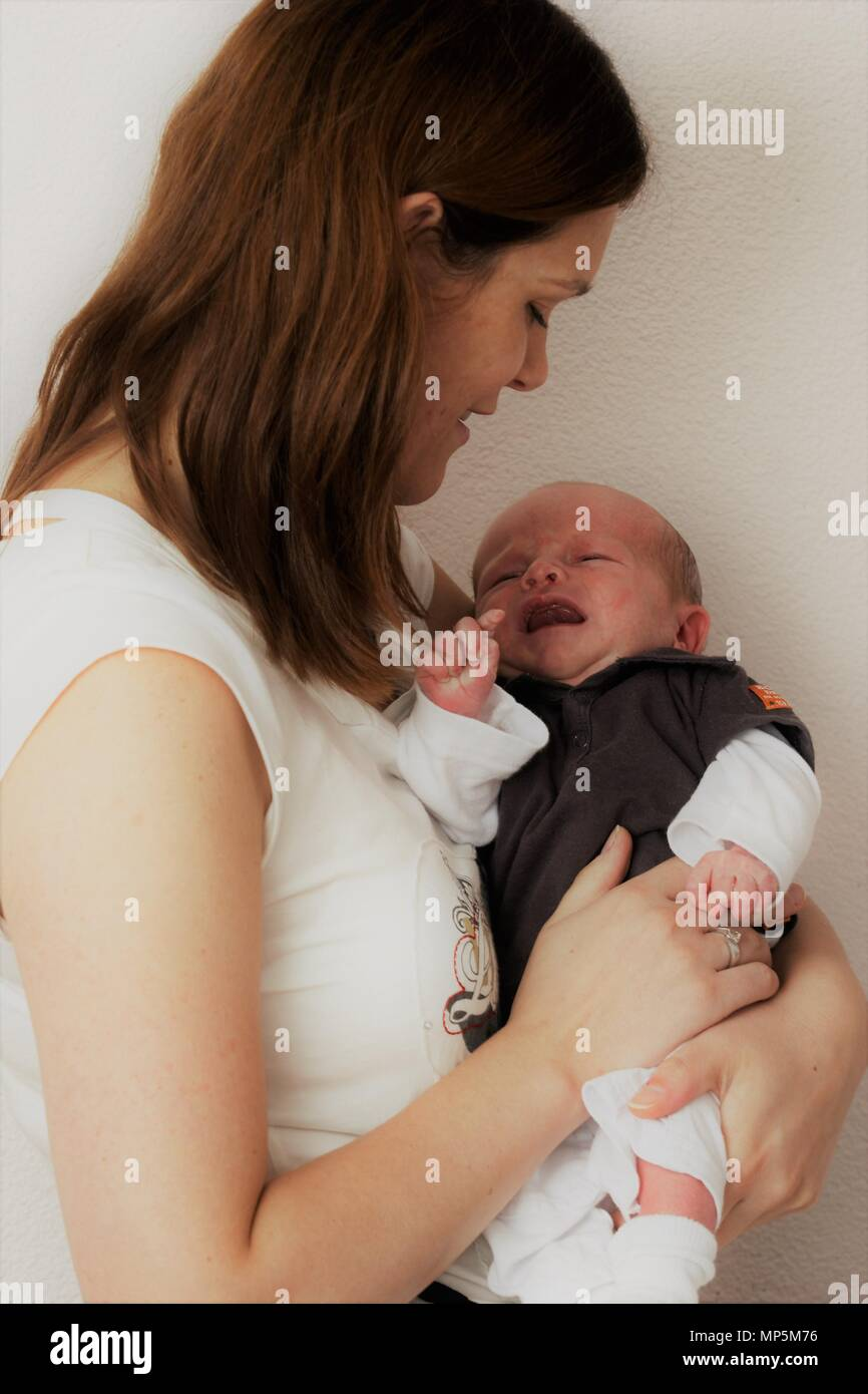Mother soothing discontent colic newborn baby boy at home, coping baby temperament. - Stock Image