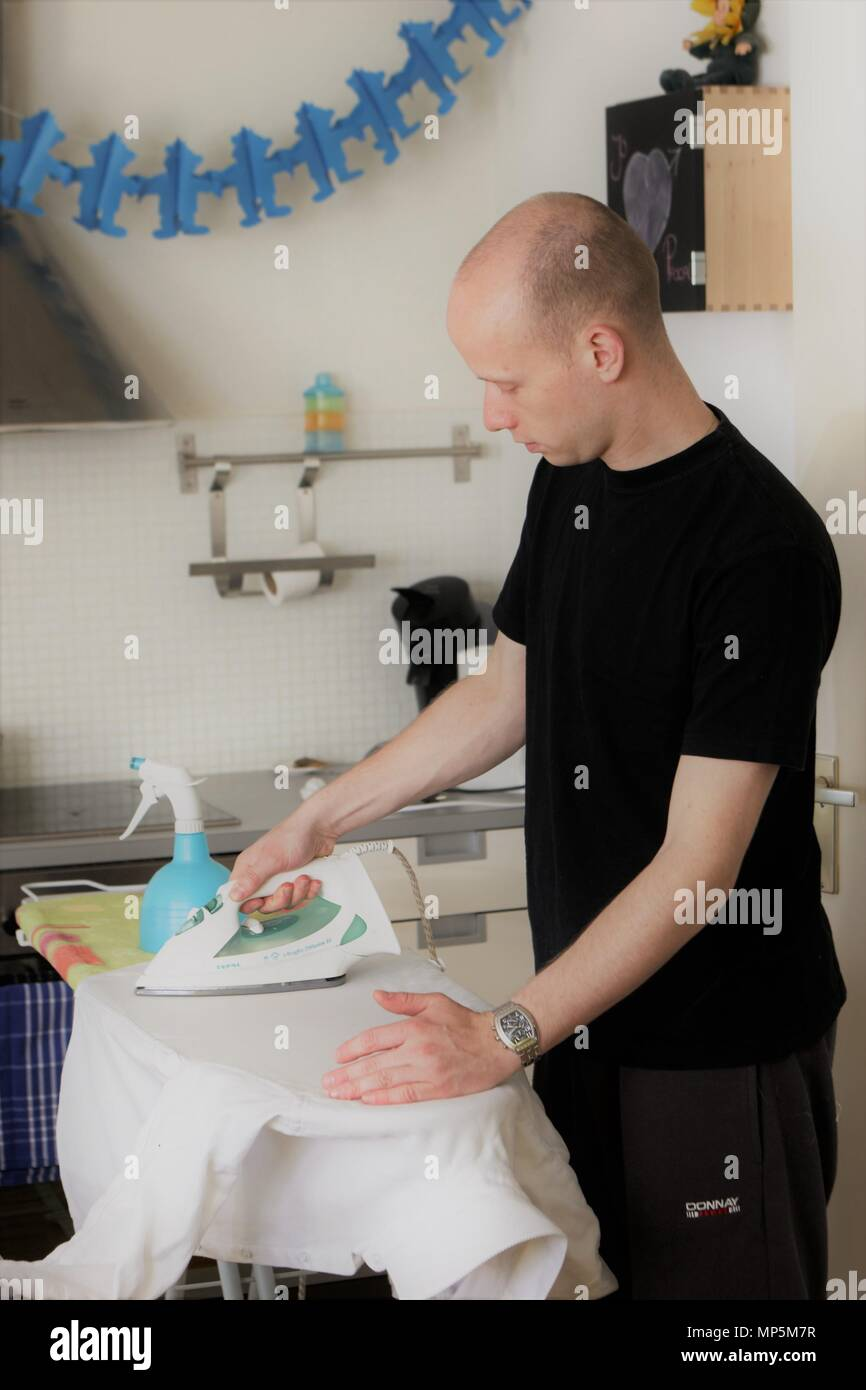 New father ironing at home due to new born family leave - Stock Image