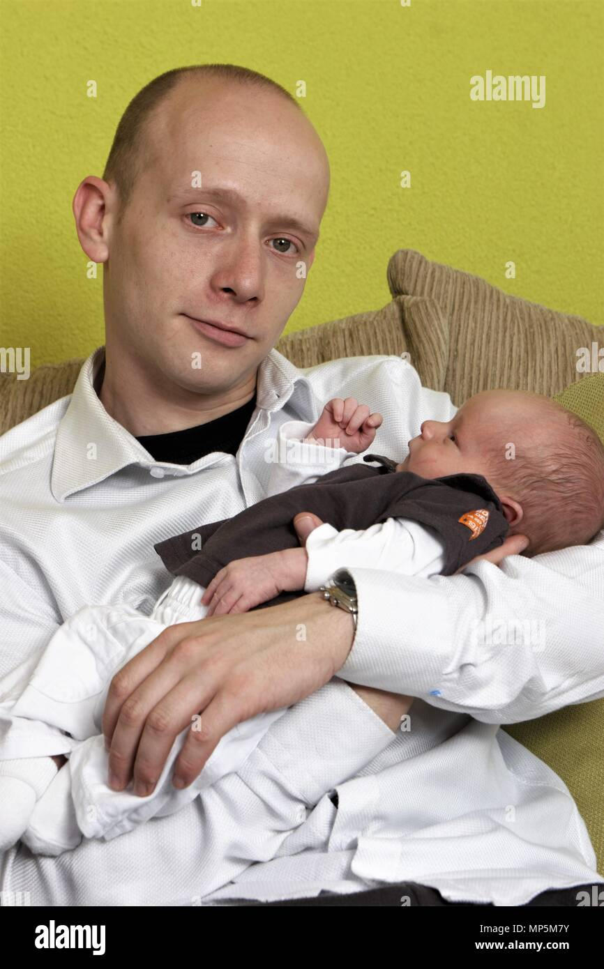 Man at parental leave holding newborn baby in his hands - Stock Image