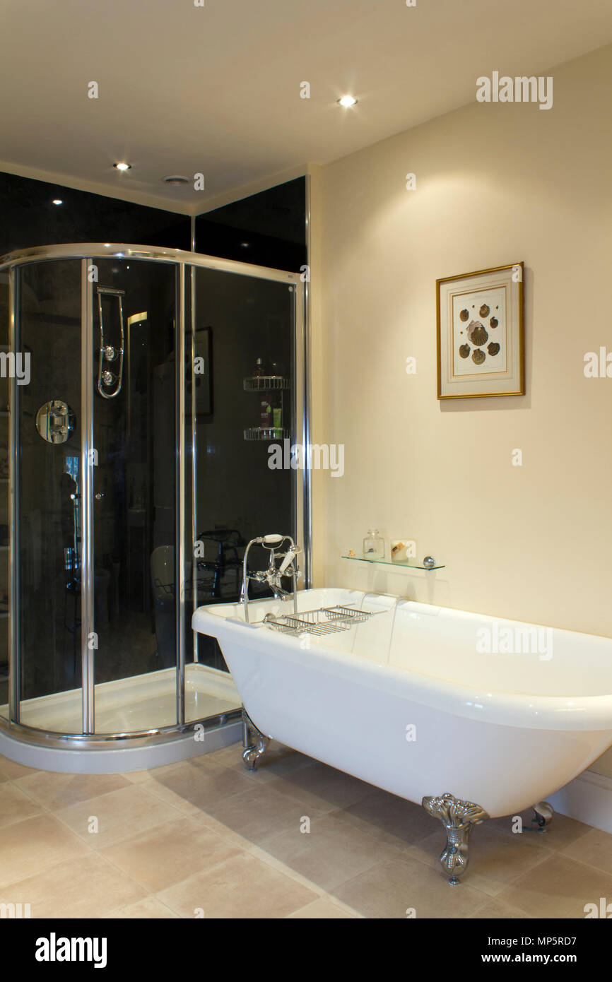 A contemporary bathroom with a glossy chrome shower cubicle and pedestal bath - Stock Image