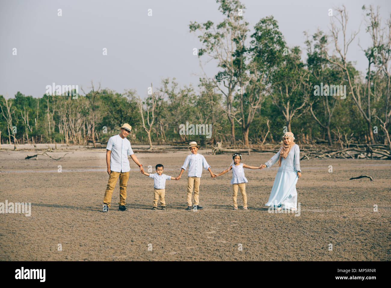 Portrait of an Asian Malaysian family looking very happy outdoors holding hand together. love and family concept - Stock Image