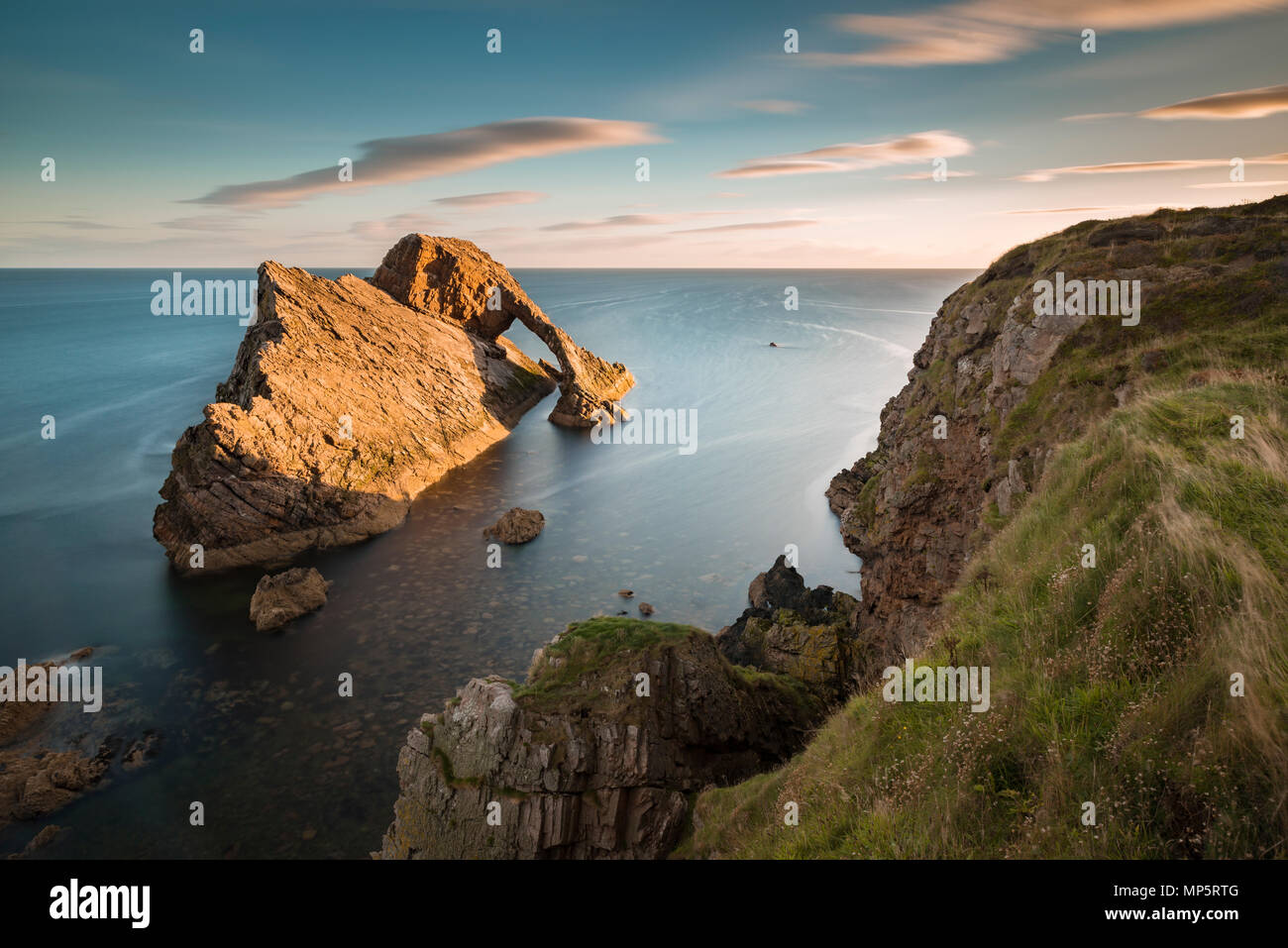 Golden light falls on Bow Fiddle Rock on the Scottish coastline at Portknockie, Moray, Scotland, UK - Stock Image