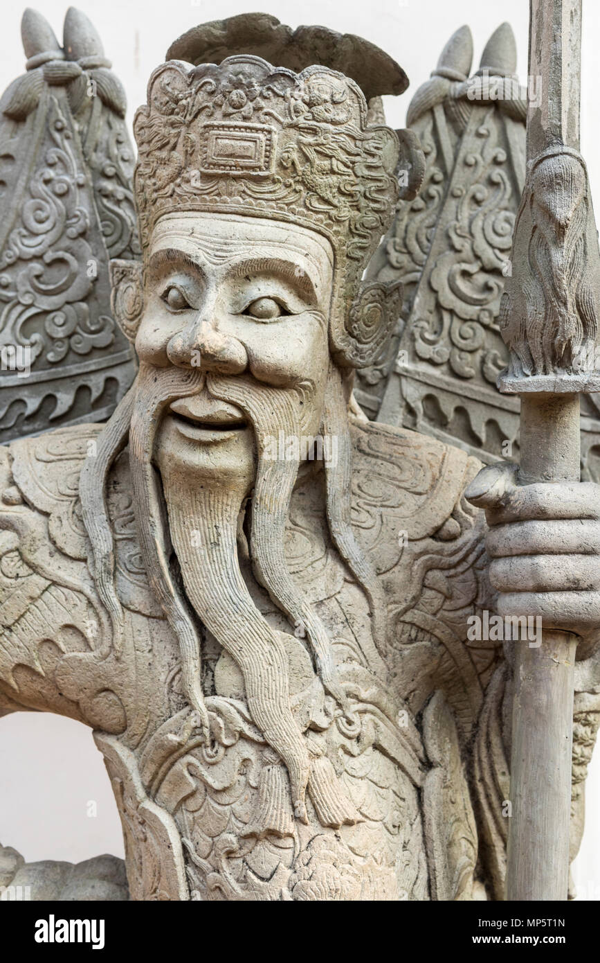 The face of a stone carving in the grounds of the Wat Pho (the Temple of the Reclining Buddha), or Wat Phra Chetuphon Bangkok Thailand - Stock Image