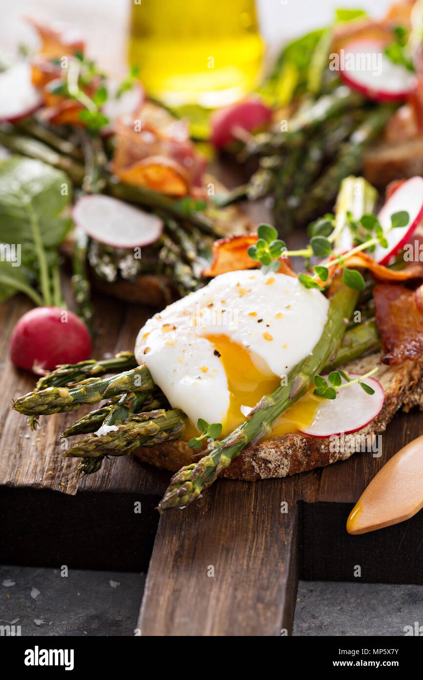 Asparagus and bacon bruschetta with poached egg - Stock Image