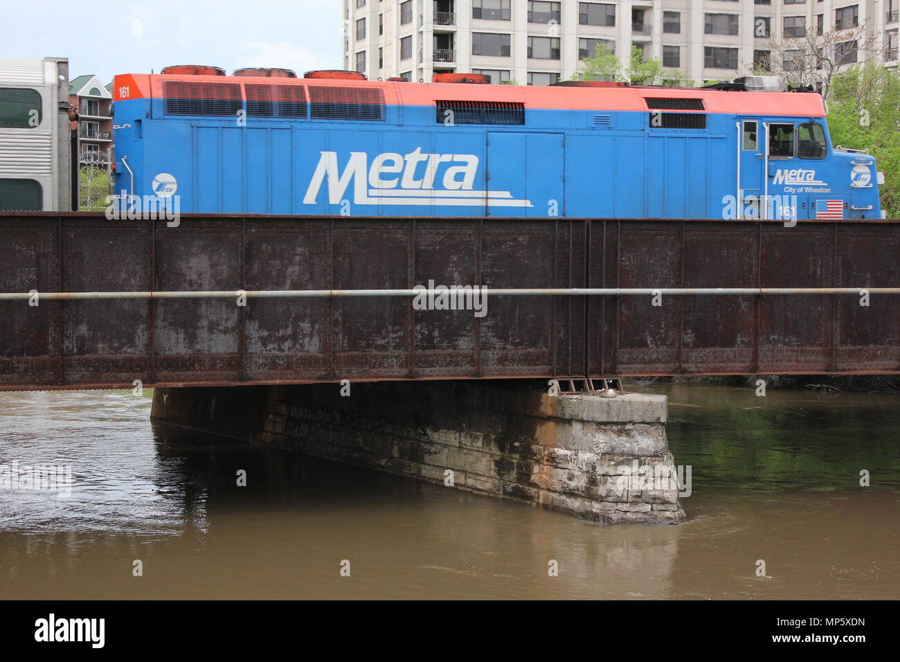 Metra train locomotive passing over a rusted bridge and stone abutment in the flooded des Plaines river. Stock Photo