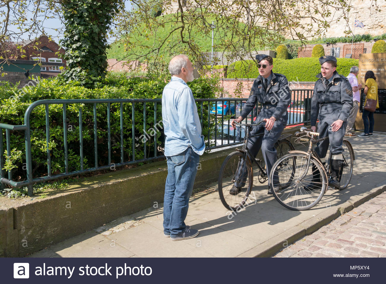 World War II re-enactors speaking to a member of the public in Lincoln town centre, Lincolnshire, UK Stock Photo