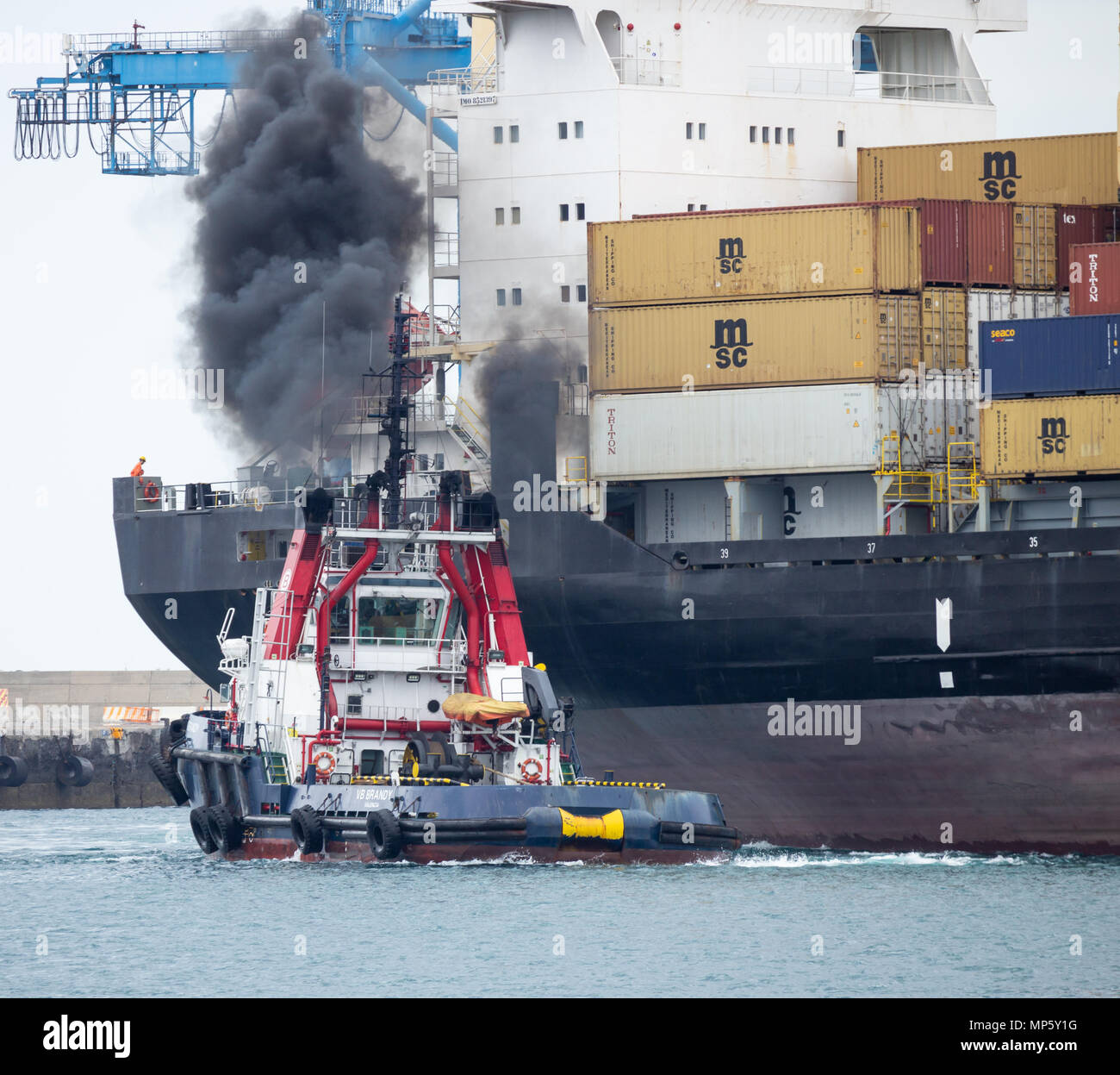 Tug boat belching out black smoke as it guides MSC Floriana container ship into port in Las Palmas on Gran Canaria Canary Islands, Spain - Stock Image