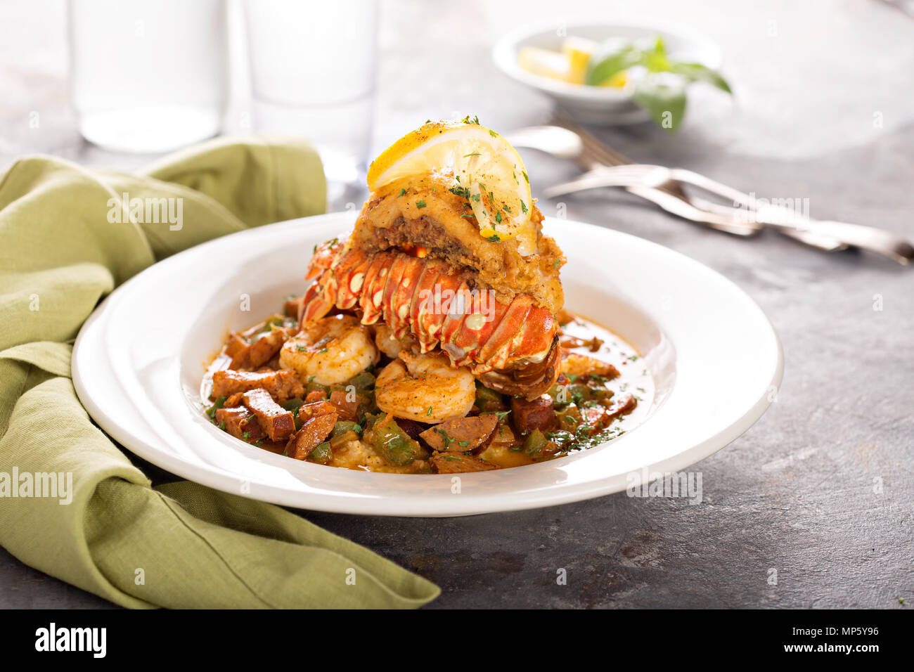 Grits with a lobster tail, shrimp and sausage - Stock Image