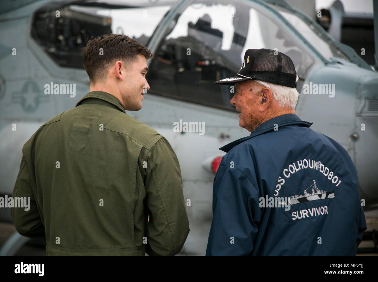 U.S. Marine Capt. Joe Hamlin gives Donald Irwin, a United States Navy World War II veteran, a tour of the Bell AH-1Z Super Cobra, April 7, 2017 on Marine Corps Air Station Futenma, Okinawa, Japan. Irwin, who served aboard a number of ships during World War II, fought at Midway and Guadalcanal and survived the sinking of the USS Colhoun during the Battle of Okinawa. Irwin returned to Okinawa and exchanged stories with the Marines and Sailors stationed on the island. Irwin is a San Jose, California native, and Hamlin, a Corbin, Kentucky, native, is a Bell AH-1 Super Cobra pilot with Marine Mediu Stock Photo