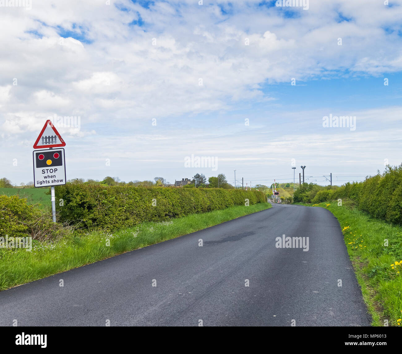 Road traffic sign warning of approaching level crossing and possible need to stop at Warkworth in Norhumberland, UK - Stock Image