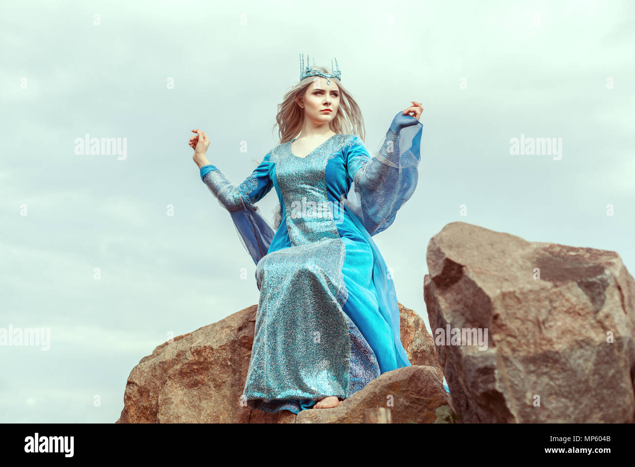 Beautiful elf woman in blue dress sits on a stone. - Stock Image