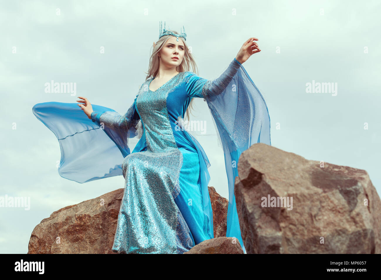 Beautiful elf woman in blue dress sits on top of a mountain. - Stock Image