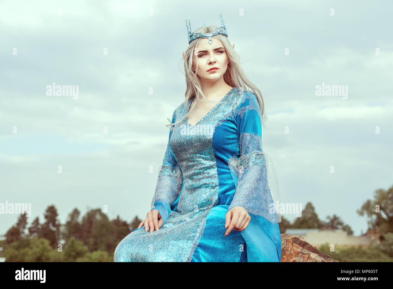 Beautiful elf woman in a blue dress sitting on top. - Stock Image