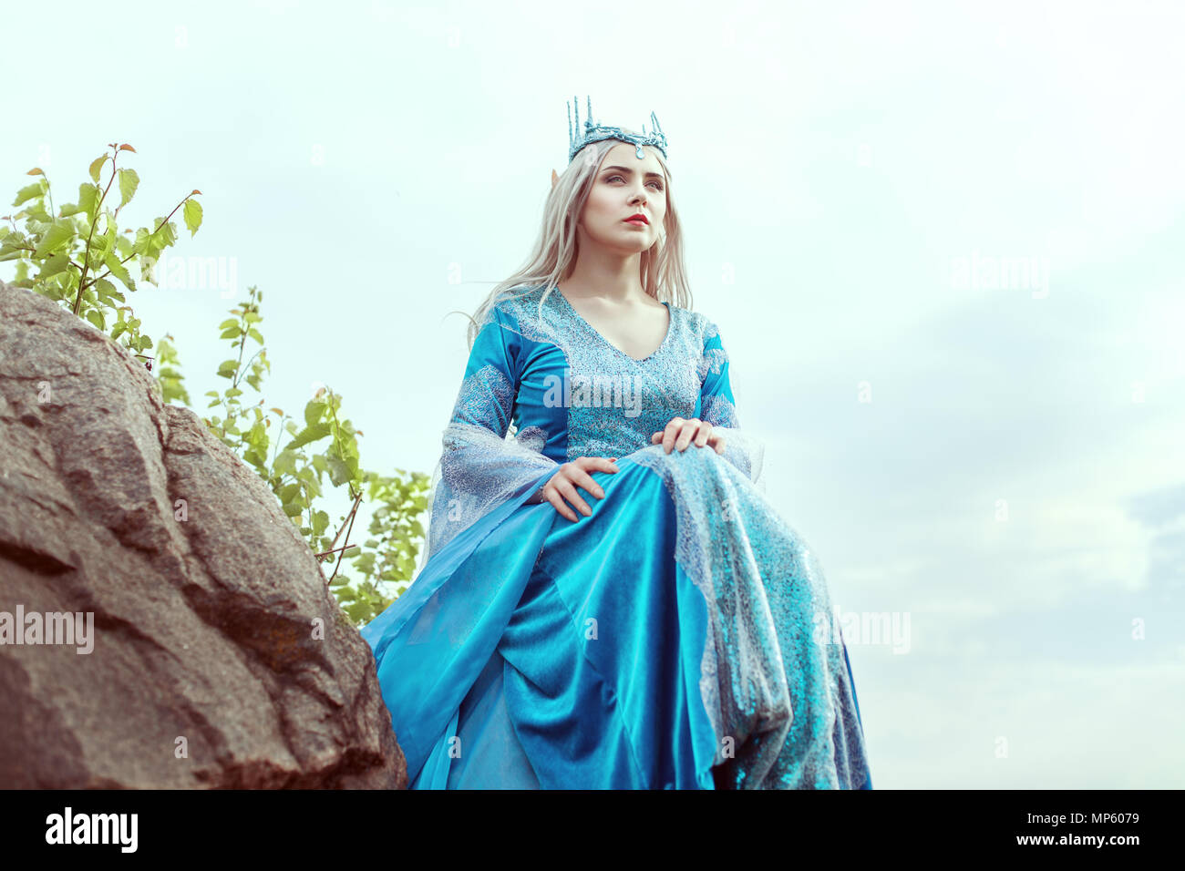 Beautiful elf woman in a blue dress is sitting on the mountain. - Stock Image