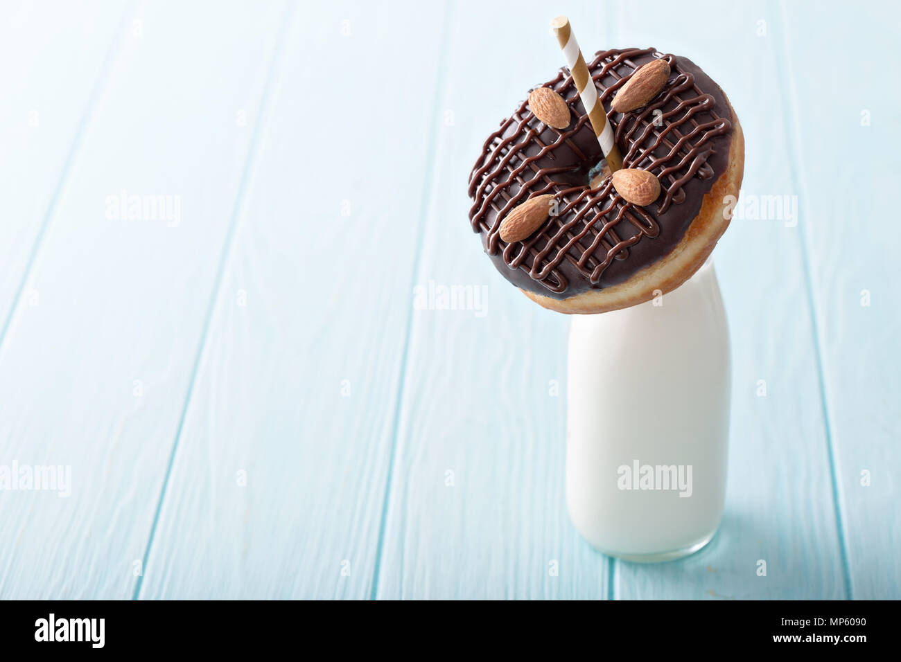 Chocolate almond donut with a bottle of milk - Stock Image