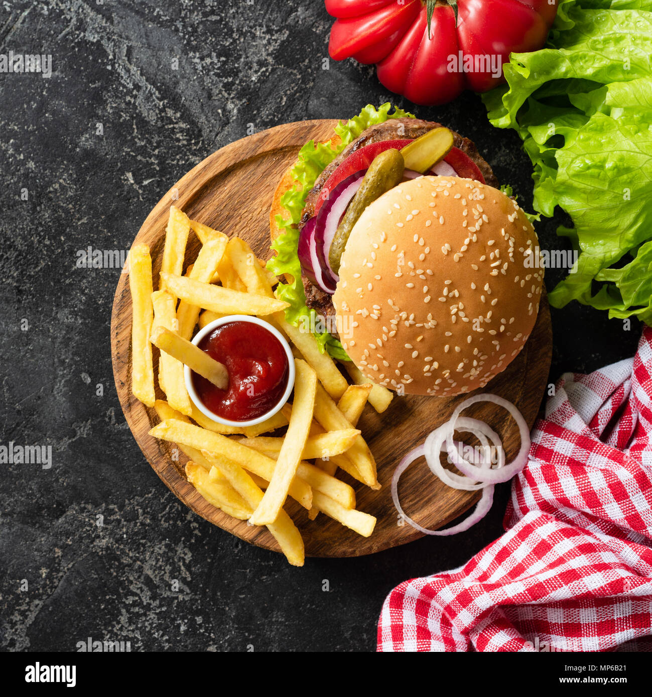 Tasty burger with beef, french fries and ketchup on dark background. Burger top view. Fast food fries and homemade cheeseburger. Square crop - Stock Image