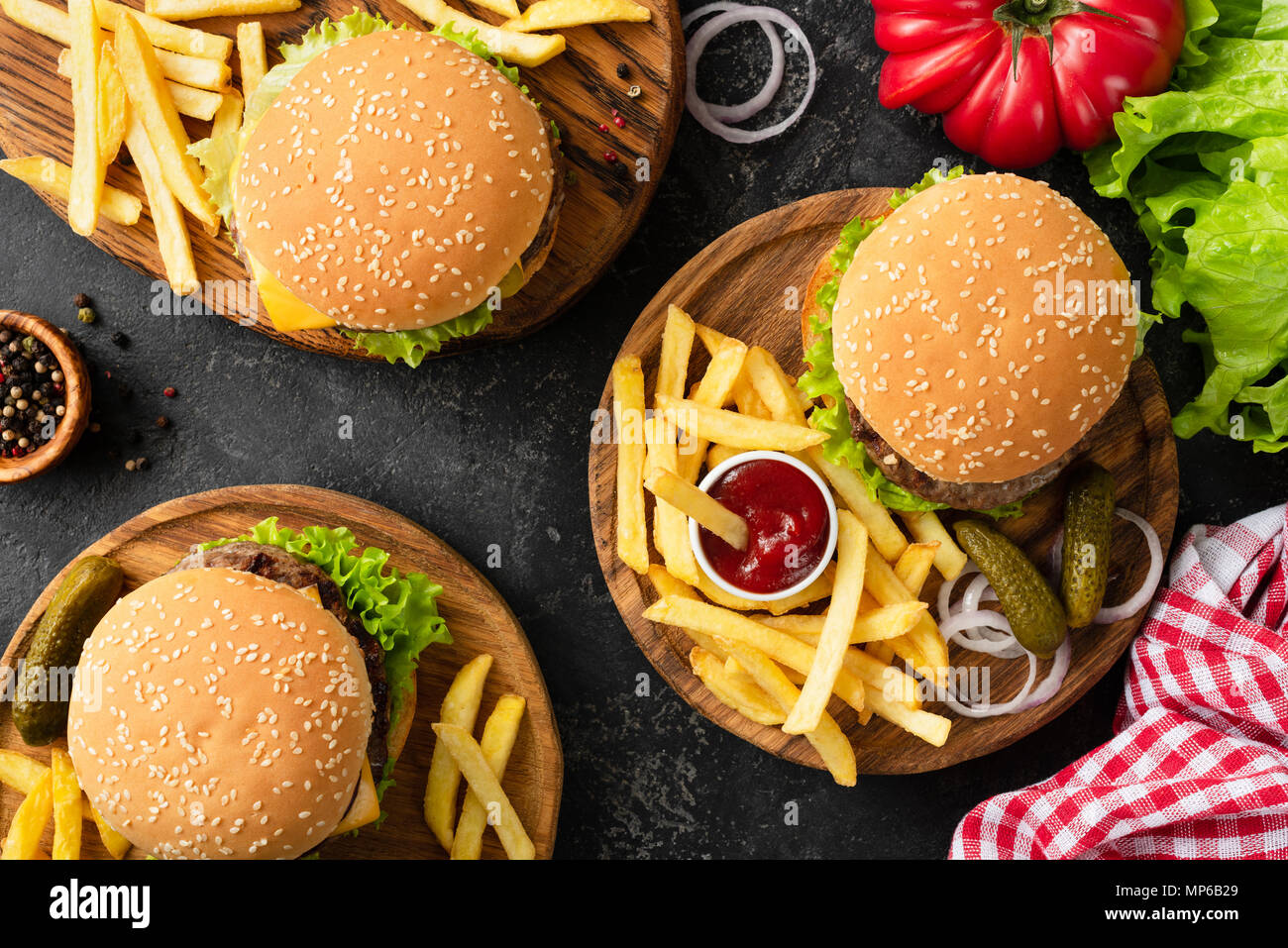 Tasty burgers, cheeseburgers, french fries, salad and red plaid kitchen textile, table top view. Three burgers or cheeseburgers, french fries and ketc - Stock Image