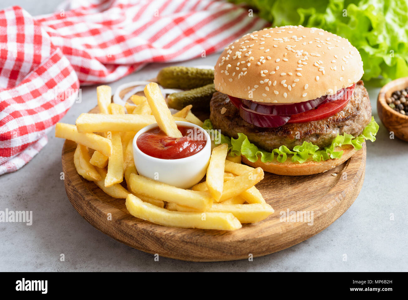Homemade beef burger and french fries with ketchup on wooden board on gray concrete background. Horizontal composition. Tasty burger and fries. Fast f - Stock Image