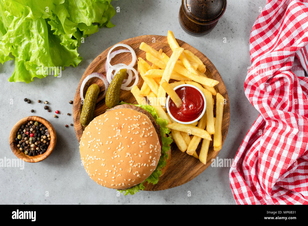 Burger with sesame, fries, pickles and lettuce salad. Top view of homemade beef burger with fries and pickles. Horizontal Stock Photo