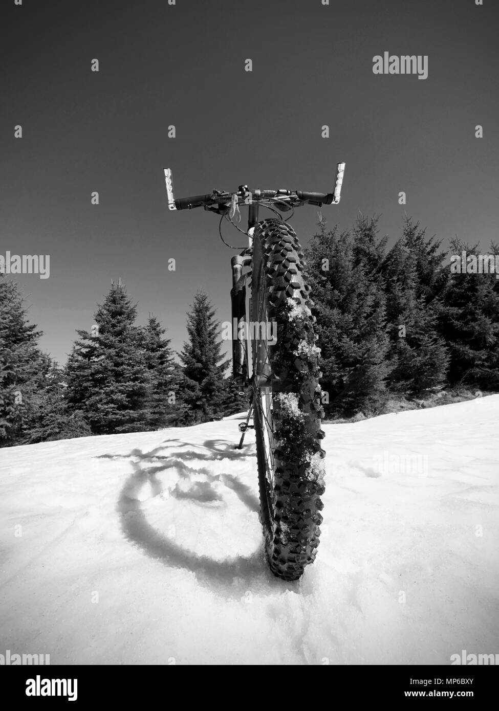 Wide view photo of mountain bike in deep snow. Winter mountains with road lost under snow. - Stock Image