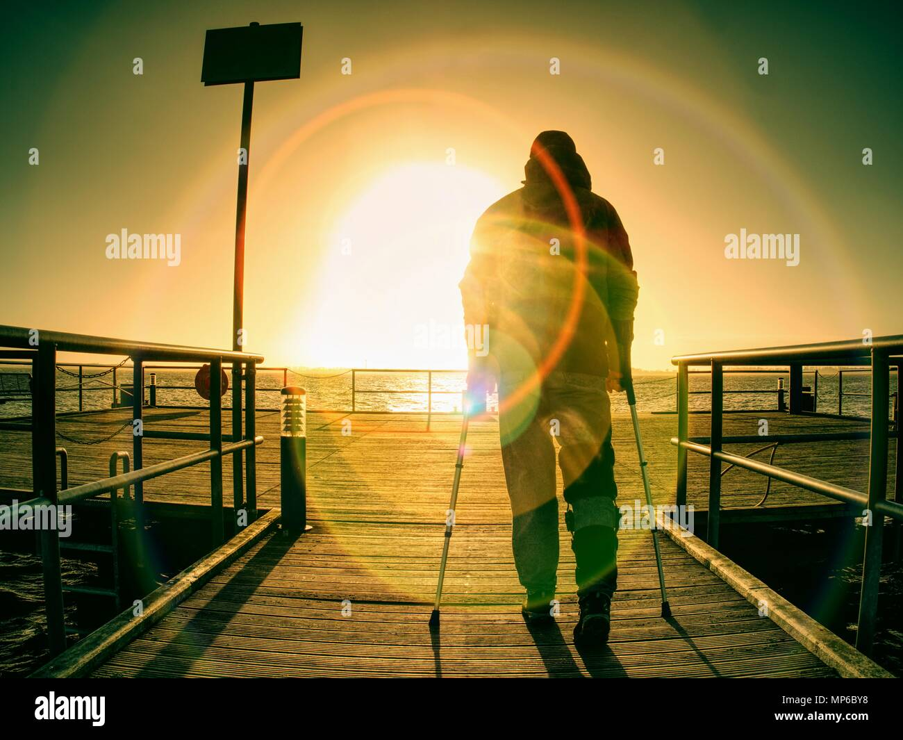 Gloomy nostalgic silhouette of sad lonely melancholic adult man with hooded jacket standing on lake bridge within  early morning and thinking - Stock Image