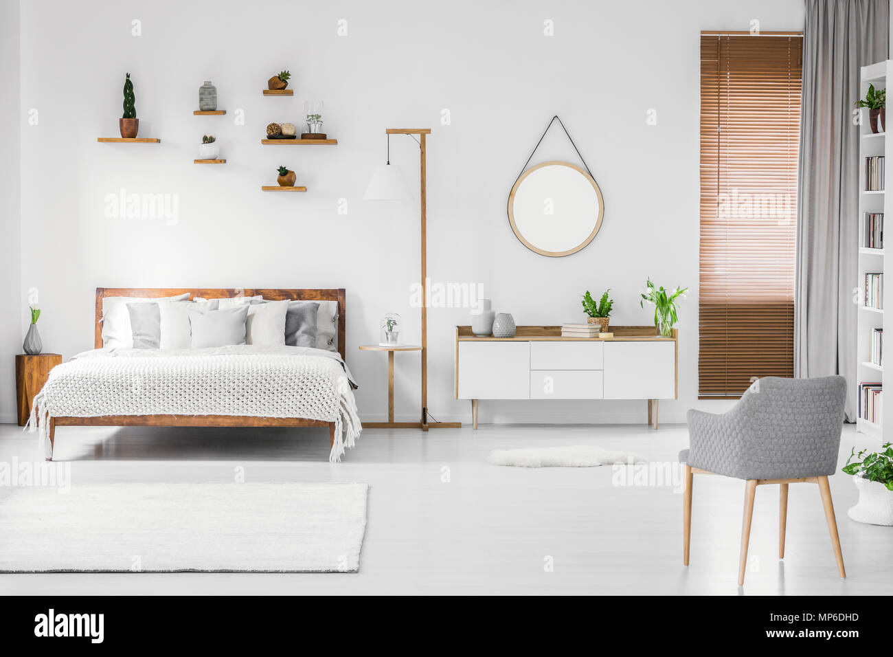 Spacious Designer White Bedroom Interior With Wooden Bed With Bedding And Pillows Night Table Small Shelves Above And Modern Armchair On The Right Stock Photo Alamy