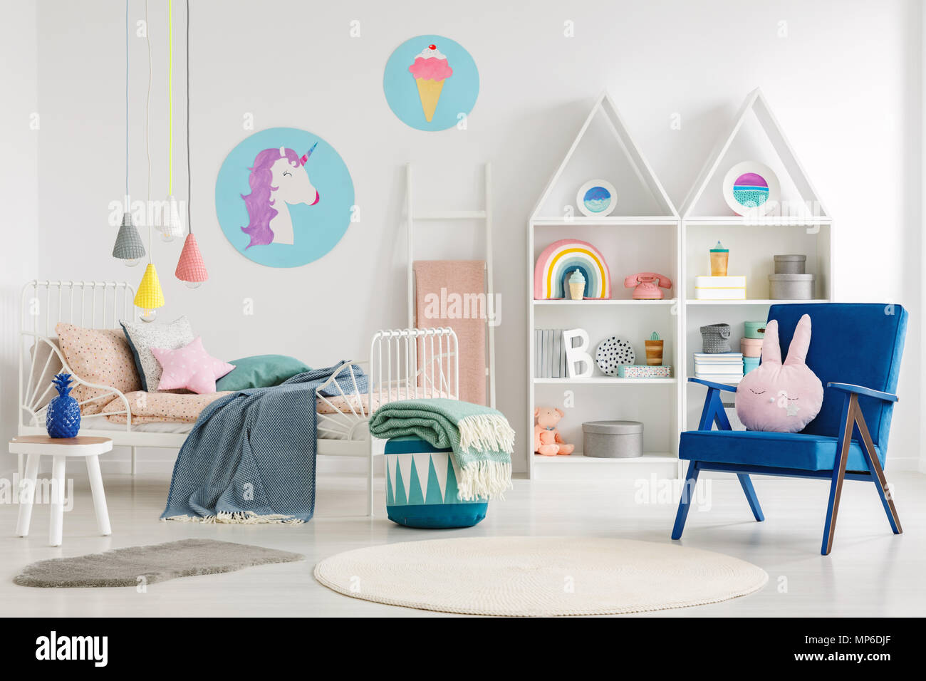 Sweet bedroom interior for a kid with a blue armchair, rabbit pillow, bed, unicorn, ice-cream posters and shelves - Stock Image