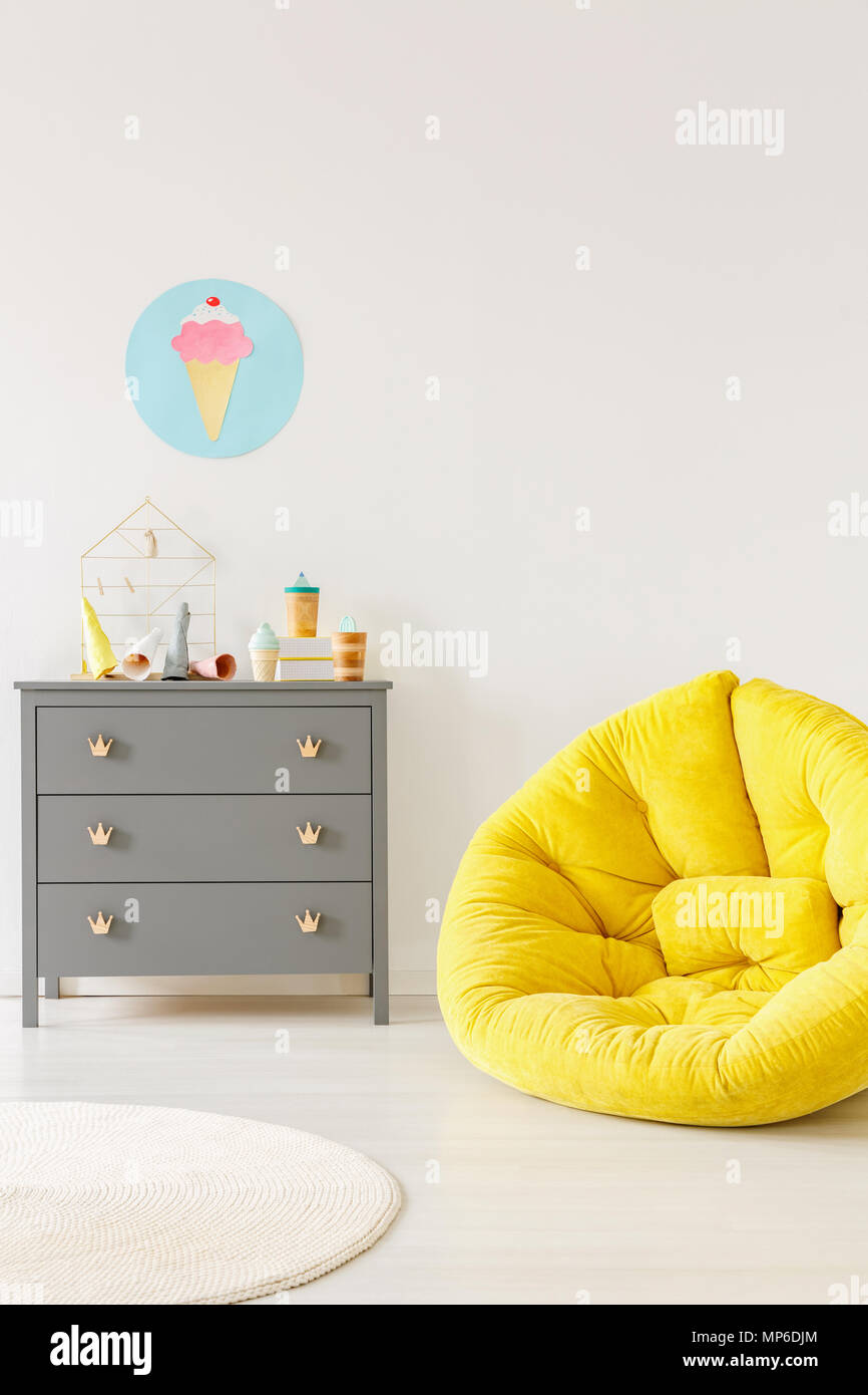 Yellow pouf next to a grey chest of drawers and ice-cream poster on ...