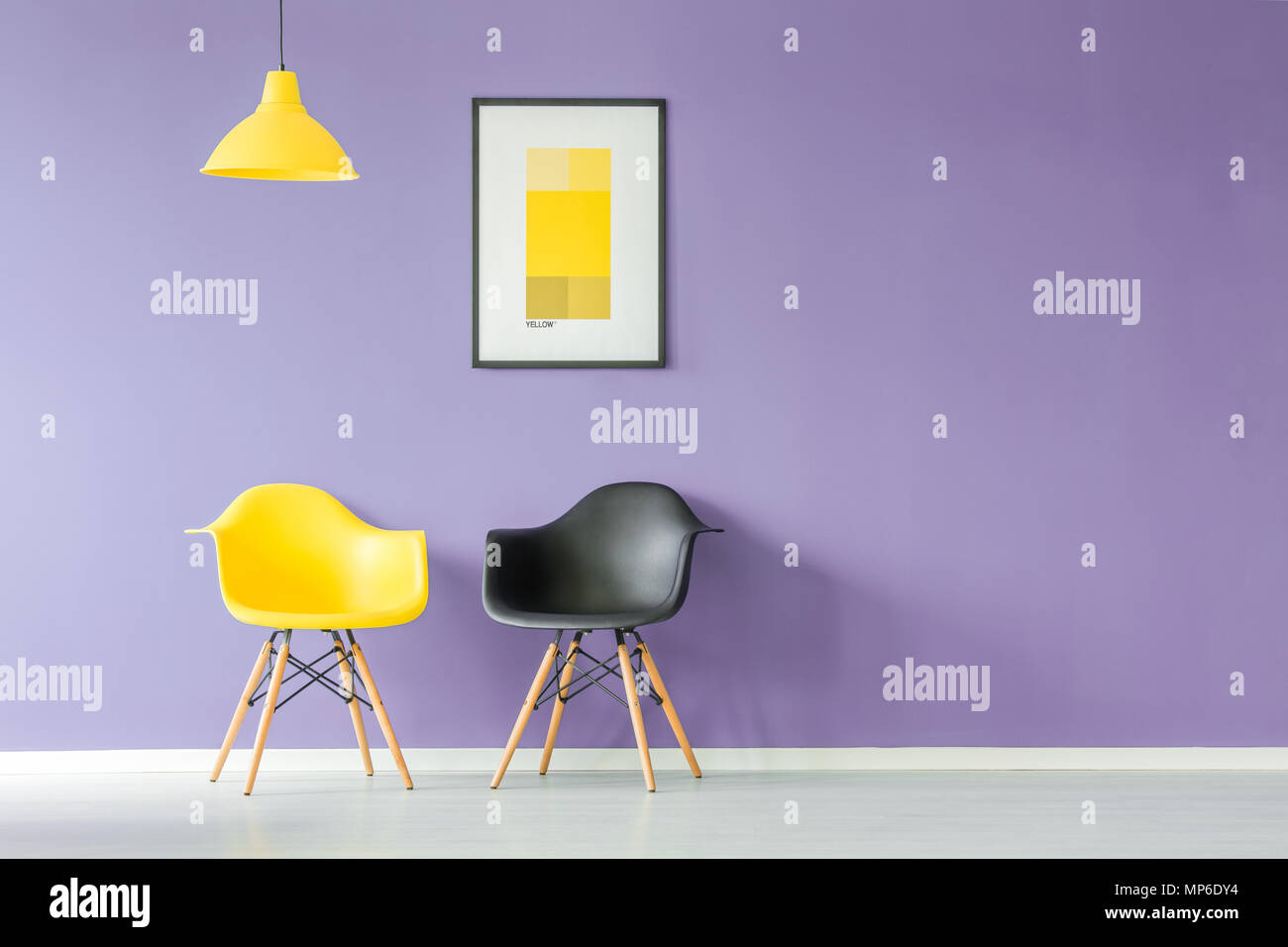 Front view of contrasting color, yellow and black chairs and a yellow lamp against purple background wall with a poster in a minimal living room inter - Stock Image