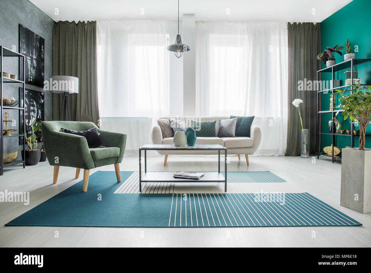 Table on green and white carpet in spacious living room interior ...